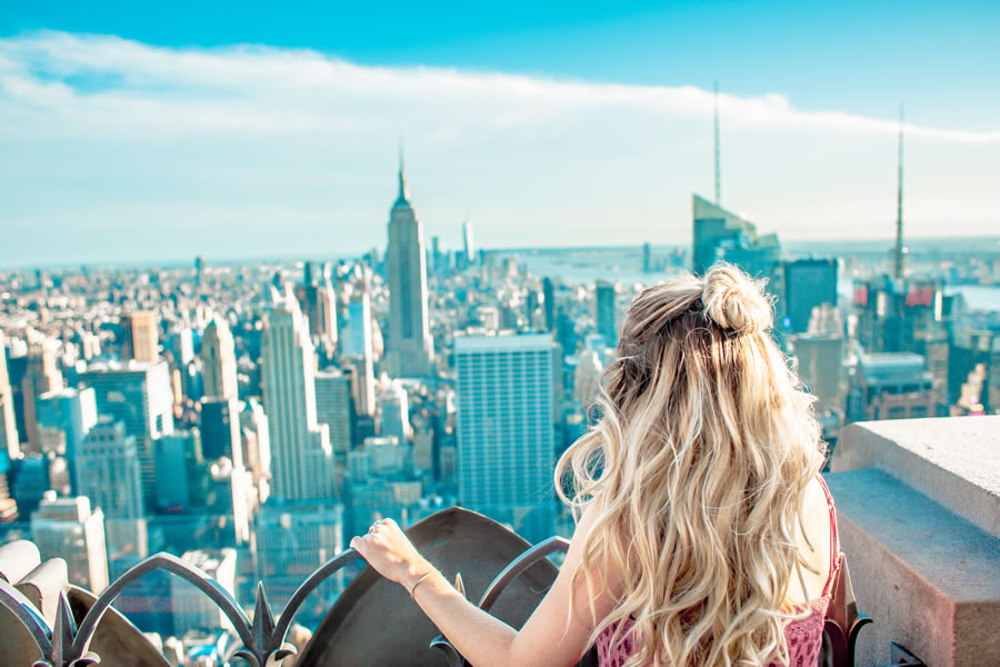 a blonde woman looking out over New York City