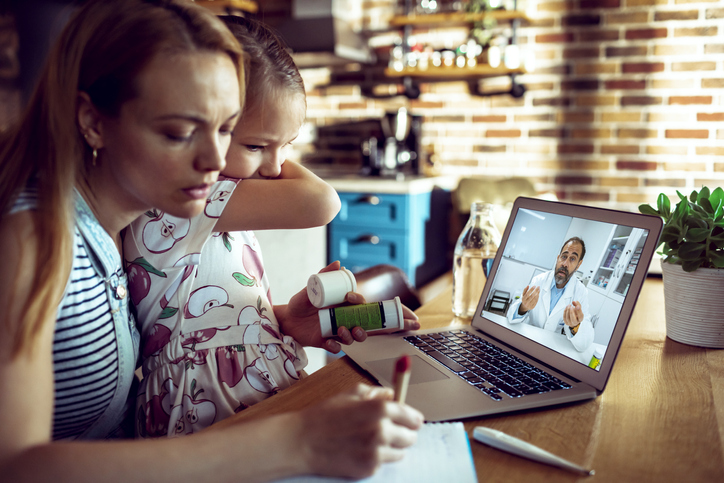 Close-up of a mother and daughter consulting their doctor during a video call on their laptop