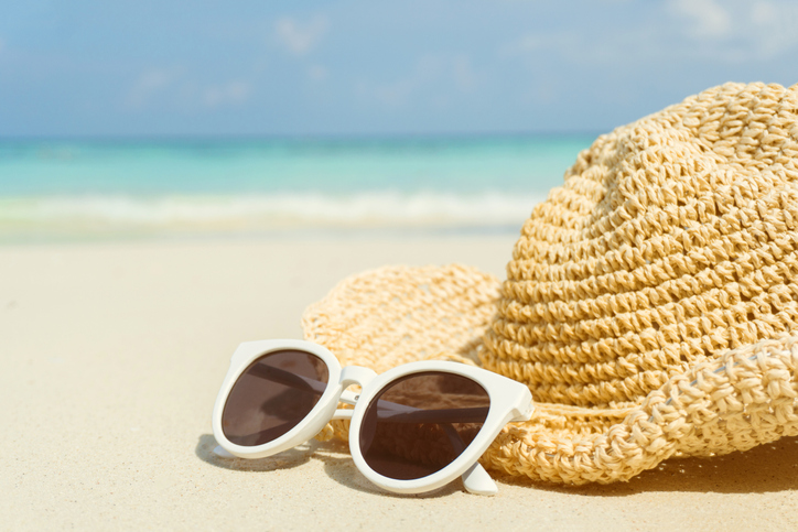 hat and sunglasses on a beach;  tinted sunscreen