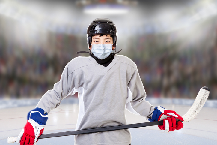Boy suited for playing ice hockey wearing a mask