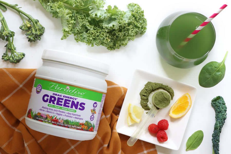 Paradise Orac Energy Greens Review next to greens and a glass with a striped straw