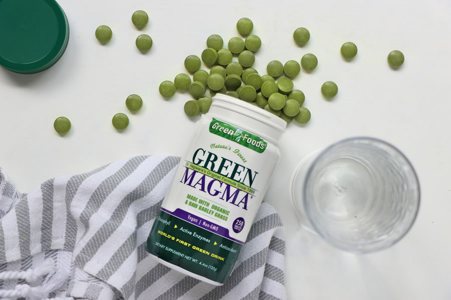 Green Magma Barley Grass Supplement flatlay with water and tablets spilled out