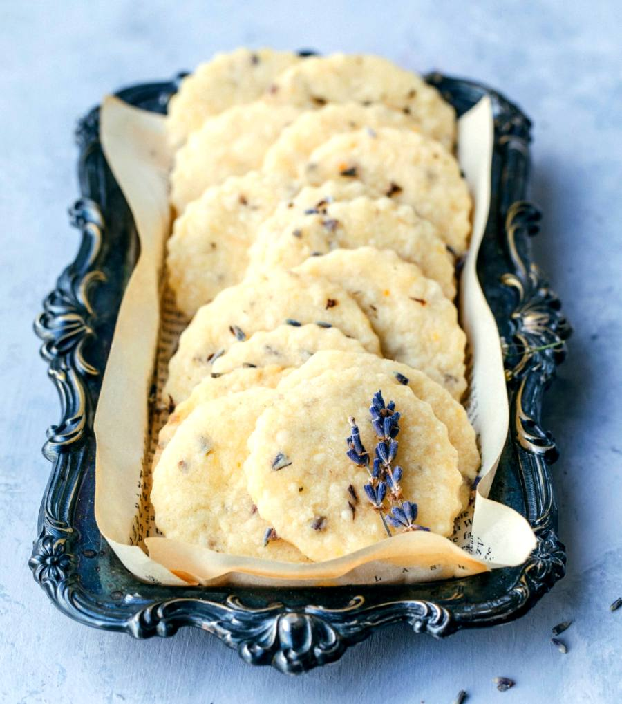 Lavender shortbread cookies arranged on an old scrolling rectangular plate with lavender sprigs