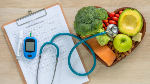 Healthy food, glucometer and clipboard to record readings, stethoscope as diabetes management concept