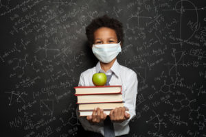 Schoolboy wearing a mask and holding school books and an apple in front of a blackboard