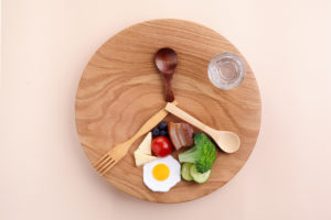Concept of intermittent fasting.  Weightloss.  Top view of plate with healthy food and glass of water.