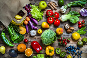 Colorful vegetables and fruits overflowing from shopping bag