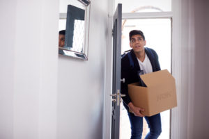 Male college student carrying a box of effects around the house