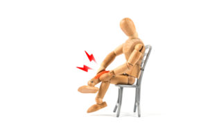 Wooden mannequin holding a painful leg;  The concept is burning neuropathy, tingling, numbness
