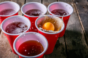 Beer pong, drinking game, ping pong ball splashing into a red plastic mug of beer