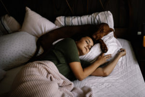 A woman and her dog asleep on her bed