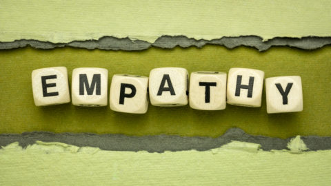 Empathy word summary in wood cubes against handmade rag paper, Ability to understand and share the feelings of another