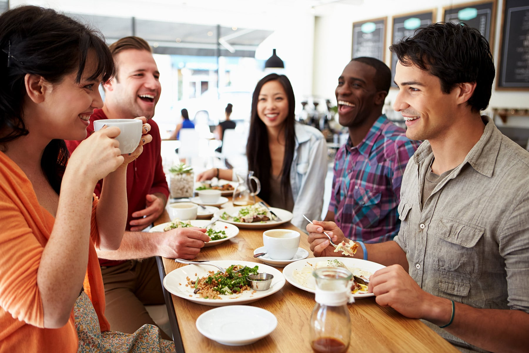 photo of adult friends eating meal in restaurant