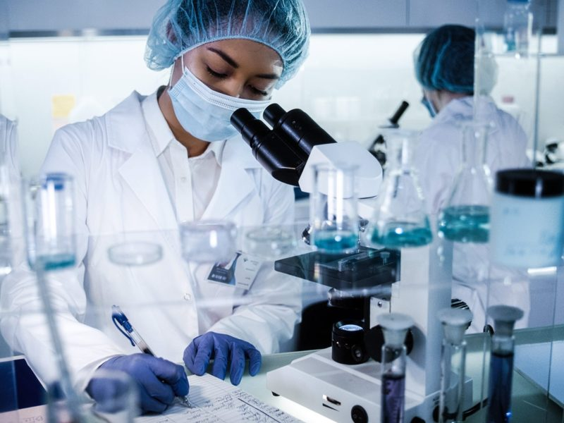 photo of medical researcher using microscope